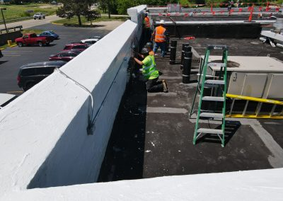 Contractors Work To Repair a Commercial Roof