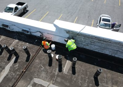 Workers Repairing and Painting Commercial Roof
